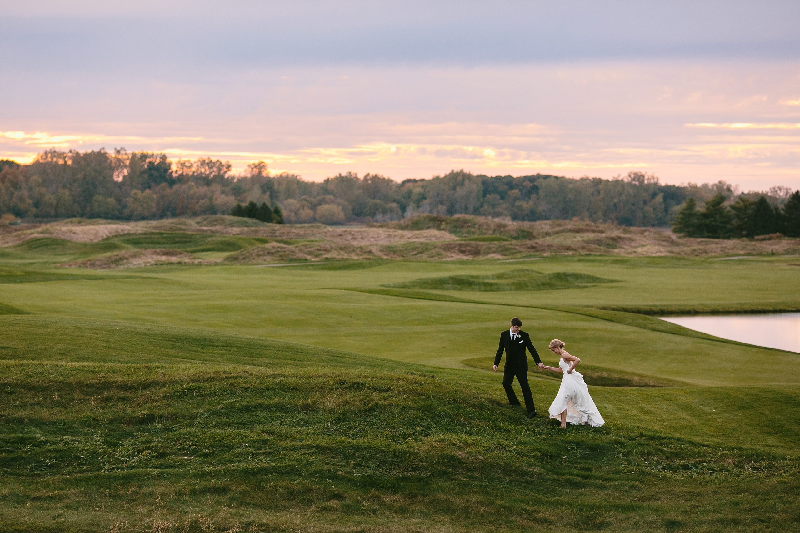 Groom leading bride up hill on a golf course during sunset.