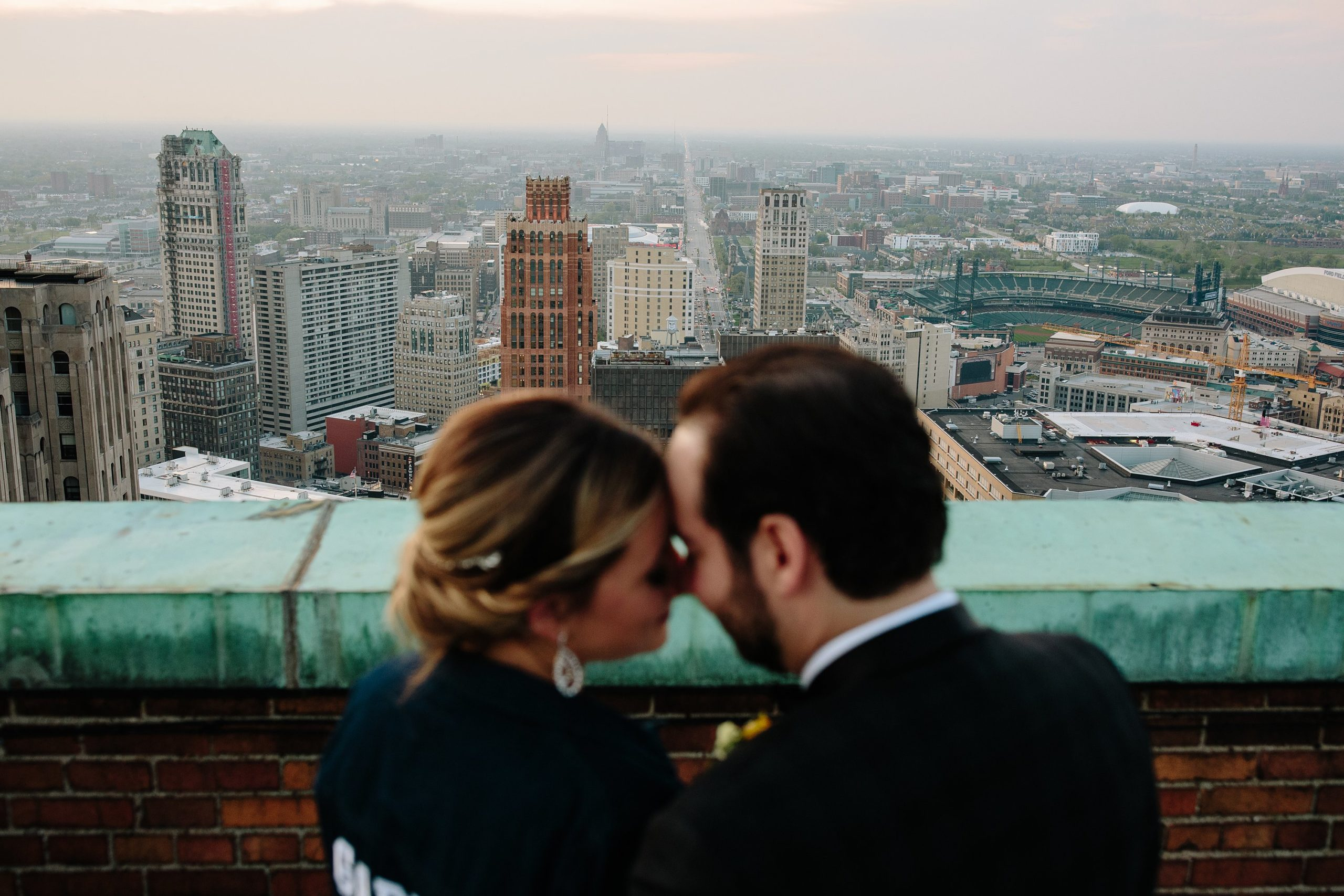 A bride and groom overlooking the city of Detroit.